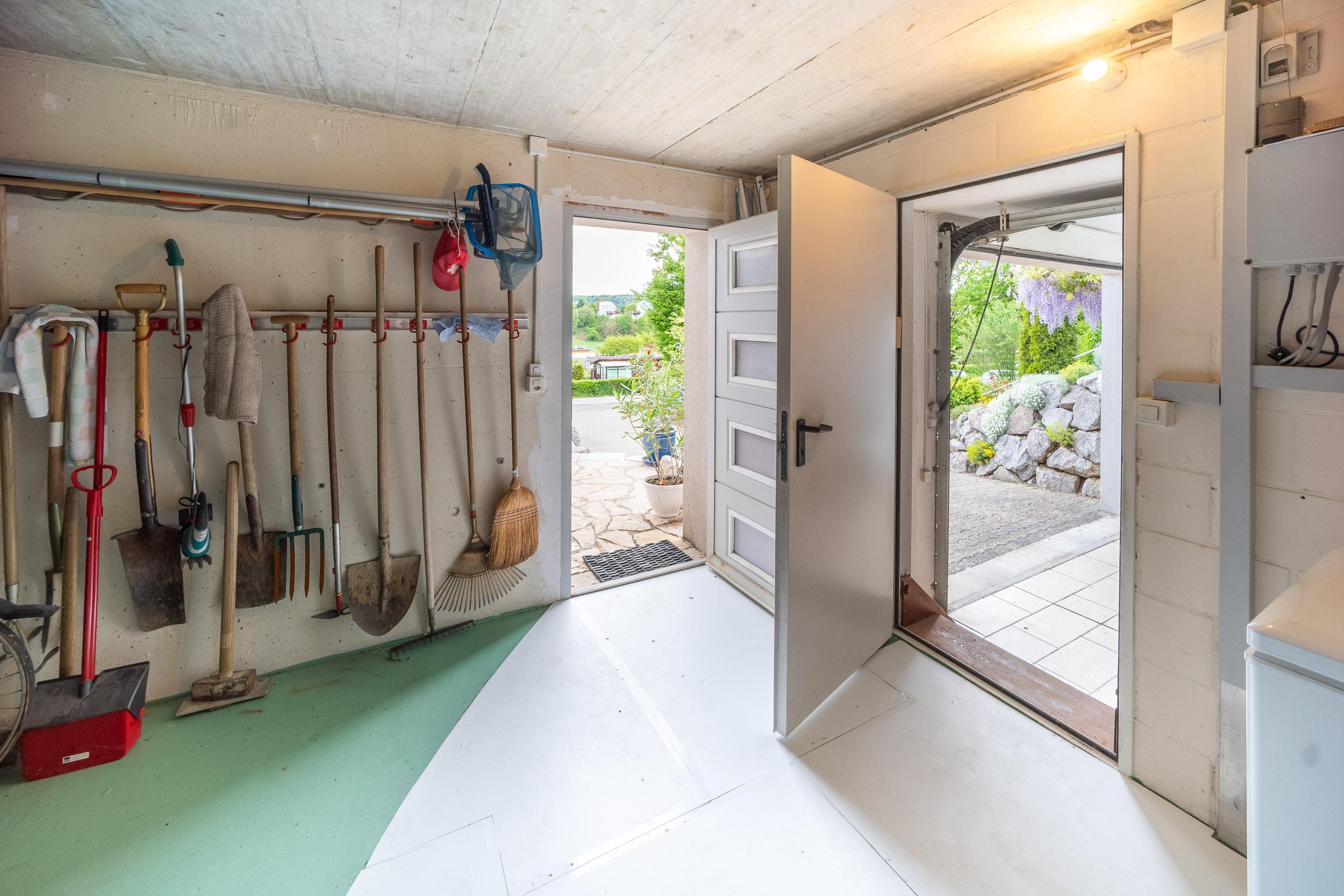 Nach der Waschküche gelangen Sie in einen Geräteraum mit Kellerabteil und Türen Richtung Garten und Garage