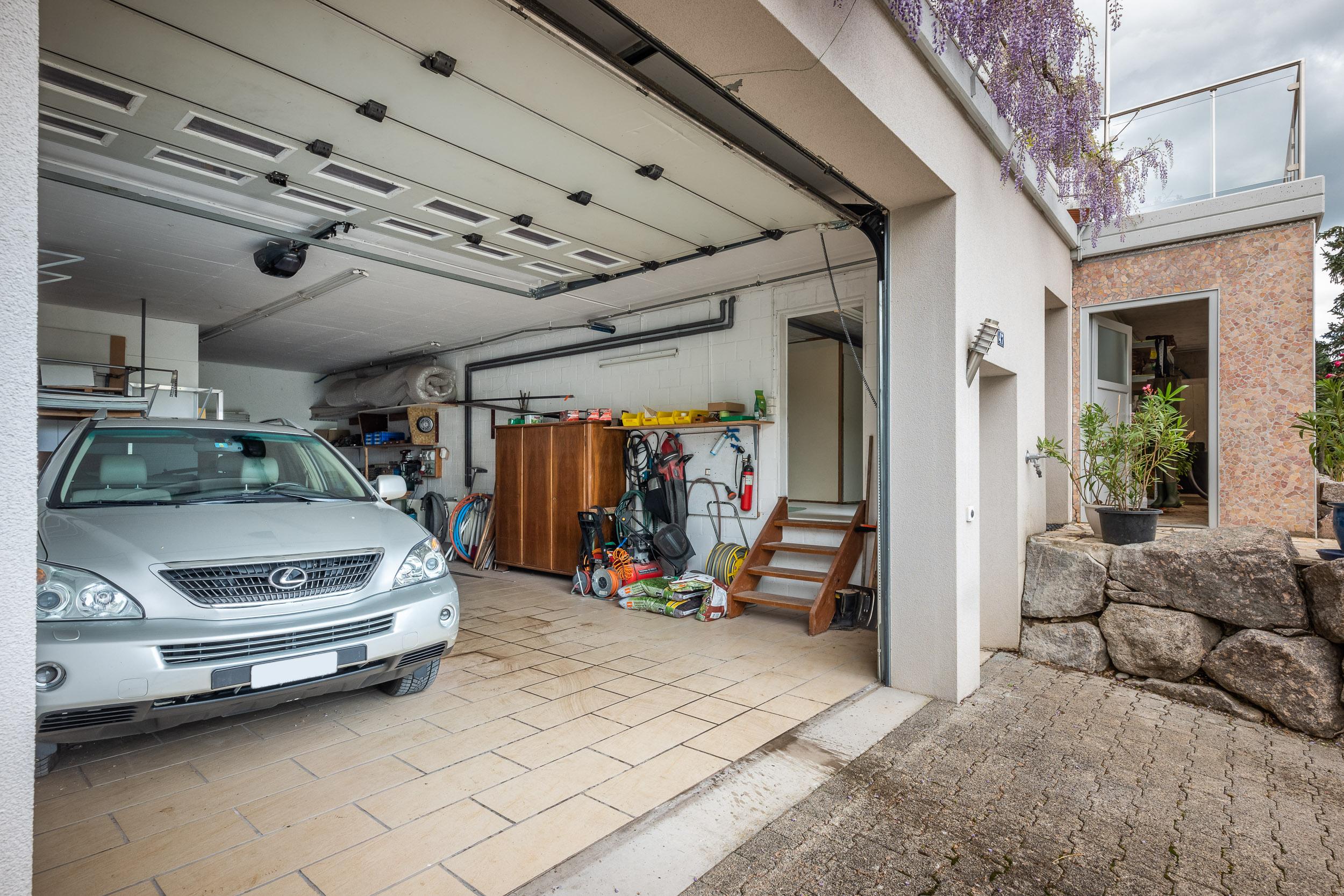 Die Garage bietet Platz für vier Autos oder ein Wohnmobil plus zwei Autos. Gleich rechts von der Garage befindet sich unterhalb der Terrasse ein Raum für Gartengeräte (s. nächstes Bild)