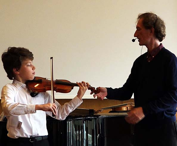 Here's Simon Fischer stabilizing a student's violin, closing the chain, perhaps to focus on a left hand concept, alignment, or bow concepts.