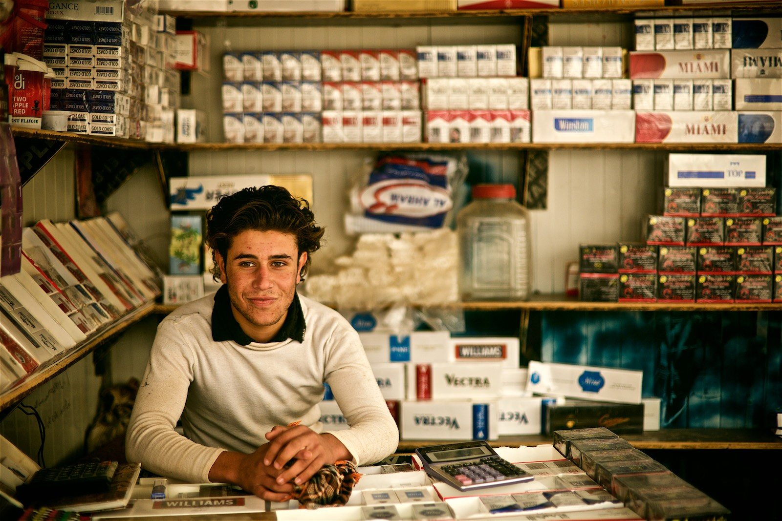 Majd, a 17-year old teenager from Dara'a, is a local cigarette vendor. He says he fled the conflict with his family and is happy to be safe, but is desperate for achieving more than just sitting in a cigarette booth.(photo: Denis Bosnic)