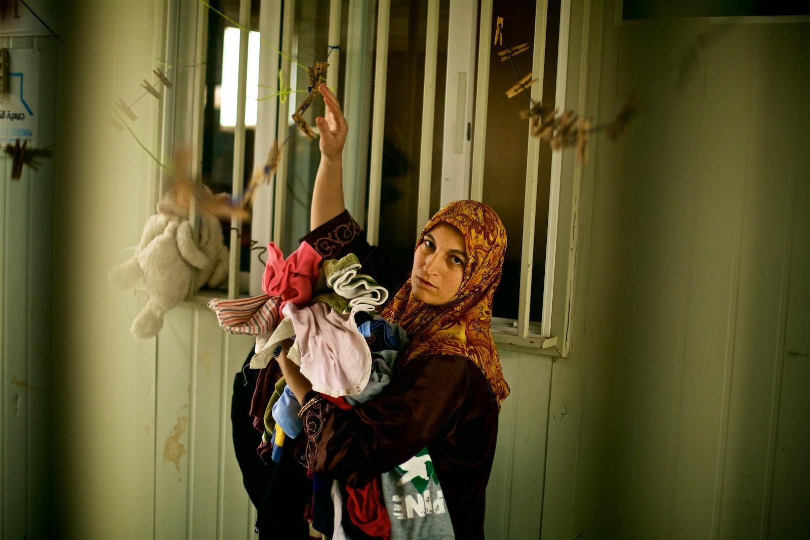 """Shayma (meno zmenené) zbiera prádlo v karavane poskytnutom UNHCR. """"Ničoho sa tu nemôžeme dotknúť. Sme tu už tri roky, ale keď nič z toho, čo tu je, nie je naše, nedá sa z toho spraviť domov."""" (photo: Denis Bosnic)"""