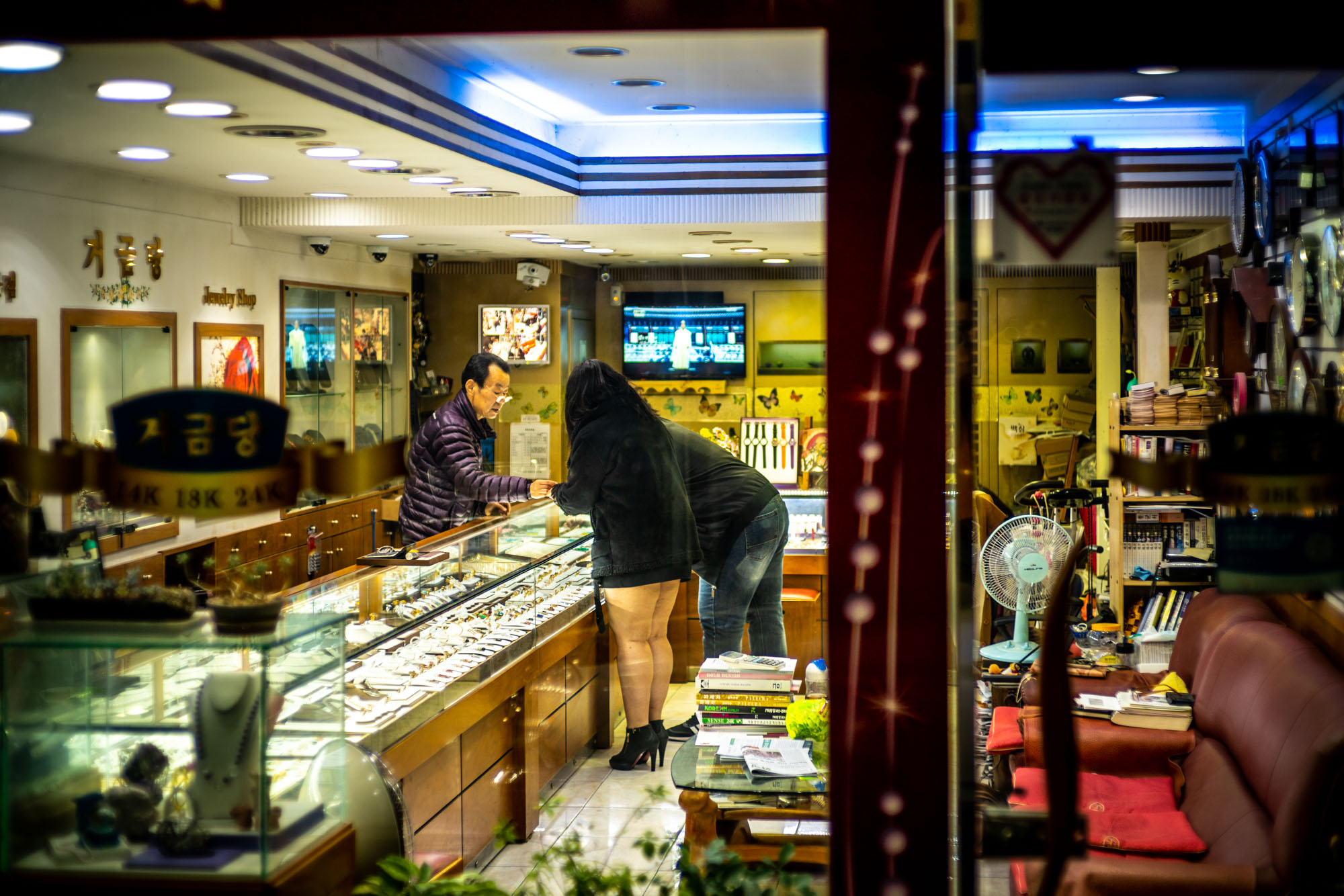 Lately, I've been noticing that my gaze has been more frequently veering towards window shops. These intentionally public viewports often frame unintentionally intimate scenes. My mind is instantly flash-flooded with imaginary stories; it can't help but attach meaning to these strangers' faces. Here, for example, a man buys his much younger lover a new ring while tiptoeing around a minefield of expectations. Both his and hers, both about the expense and the secrecy of their arrangement.