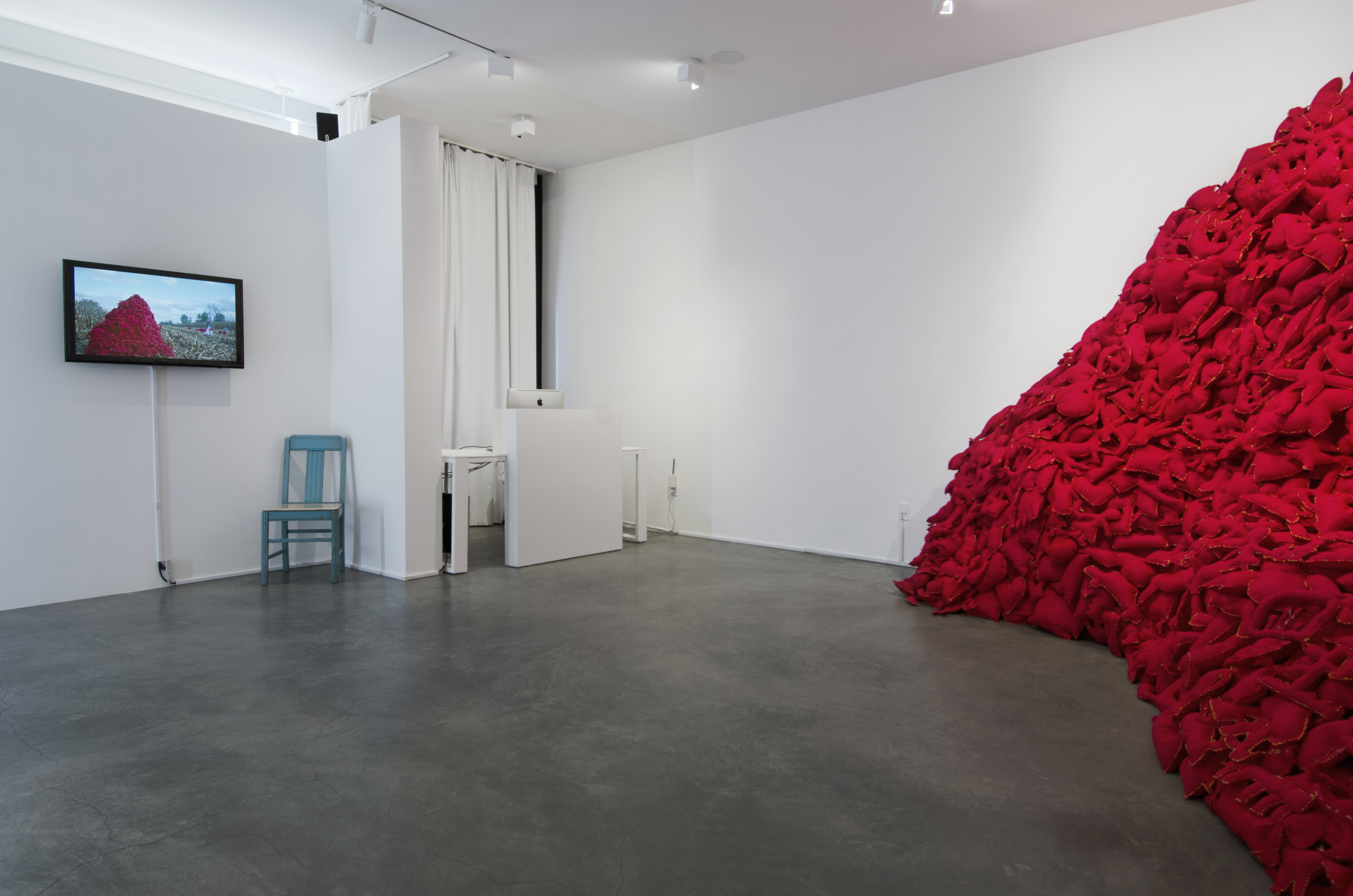 Installation View  (Shulamit Gallery, 2014)   The Pile,  2014 Single Channel HD Video Projection with Sound (16mm Film), TRT 12:00, Looping; Digital C-Prints; Hand-Stitched Red Felt Objects Installation Dimensions Variable