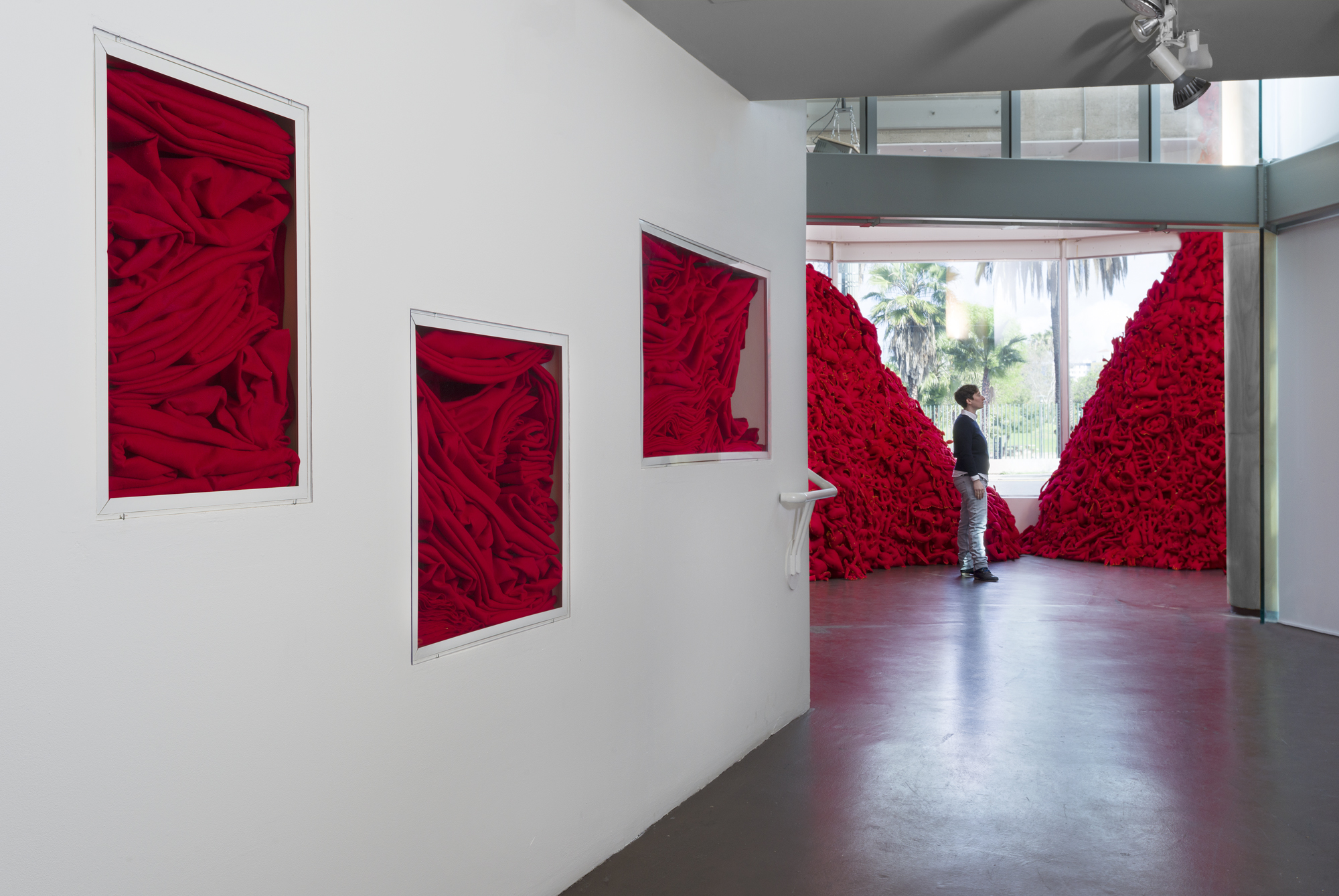 Installation View  (Craft & Folk Art Museum, 2015)   The Pile,  2014 Single Channel HD Video Projection with Sound (16mm Film), TRT 12:00, Looping; Digital C-Prints; Hand-Stitched Red Felt Objects Installation Dimensions Variable