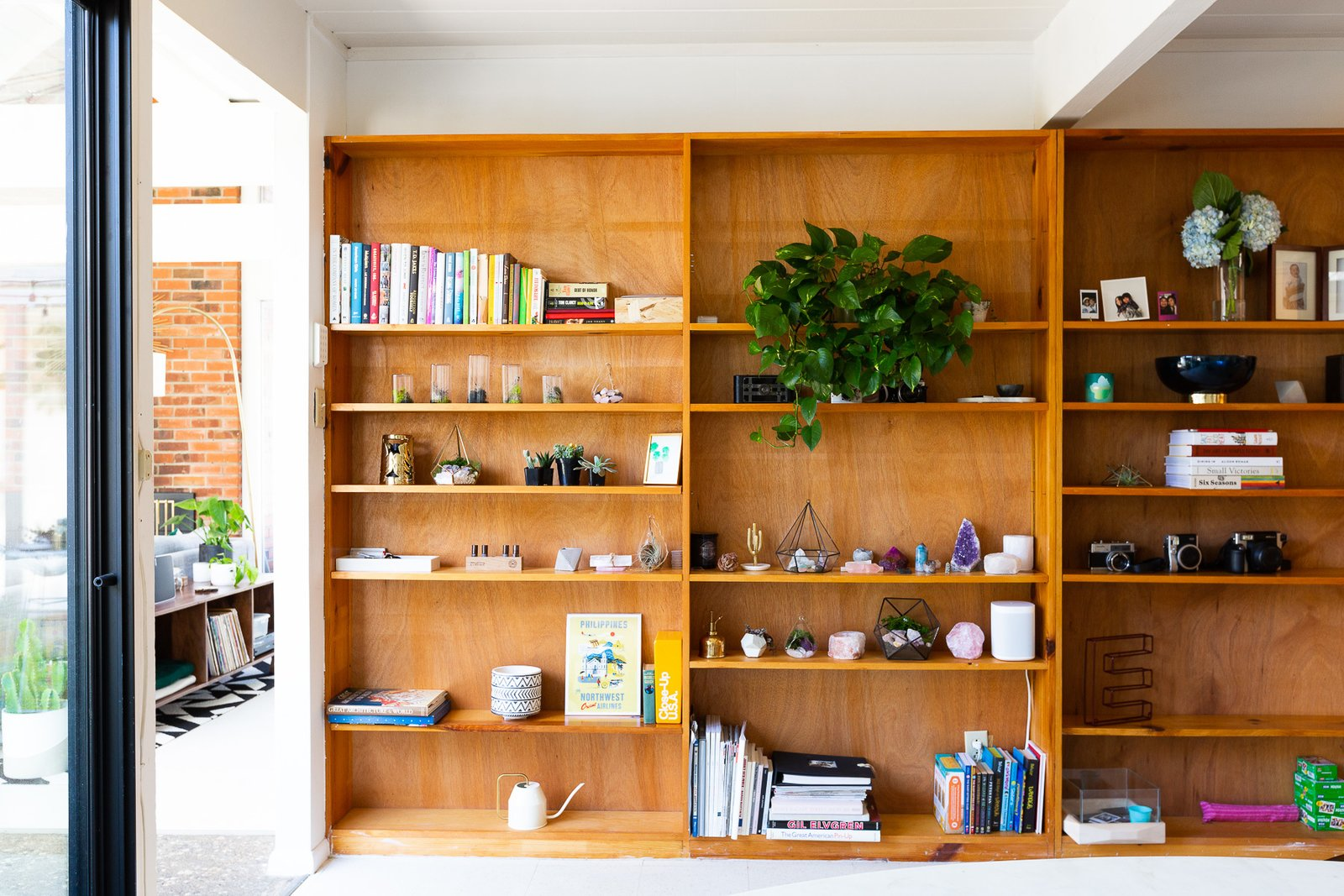 The bookshelf across from the breakfast nook holds favorite books, crystals, plants, and vintage cameras. (Gillian Walsworth)