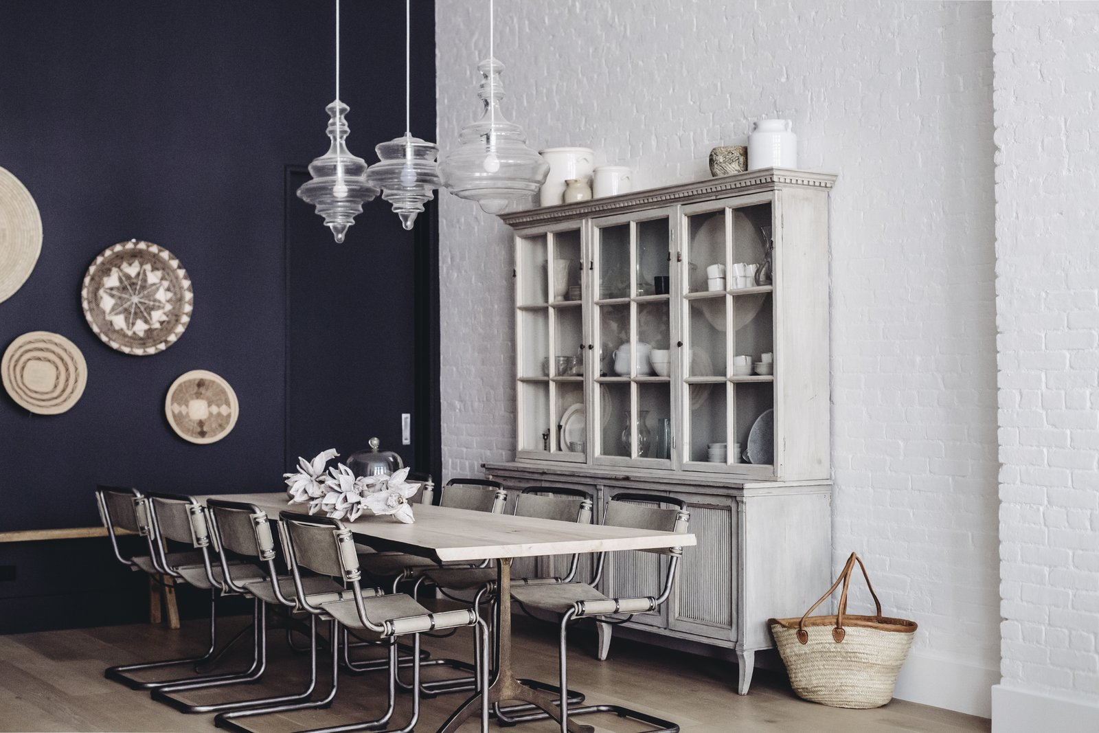 """The dining room melds a modern accent wall swathed in """"Railings"""" paint by Farrow and Ball with hanging wall baskets from Habitat Greenwich, bold pendants by Hudson Valley Lighting, and an antique hutch from Lone Ranger Antiques. In the center sits a dining table, custom created with Studio Endo, and chairs from Sarreid. (Chloe Leroux)"""