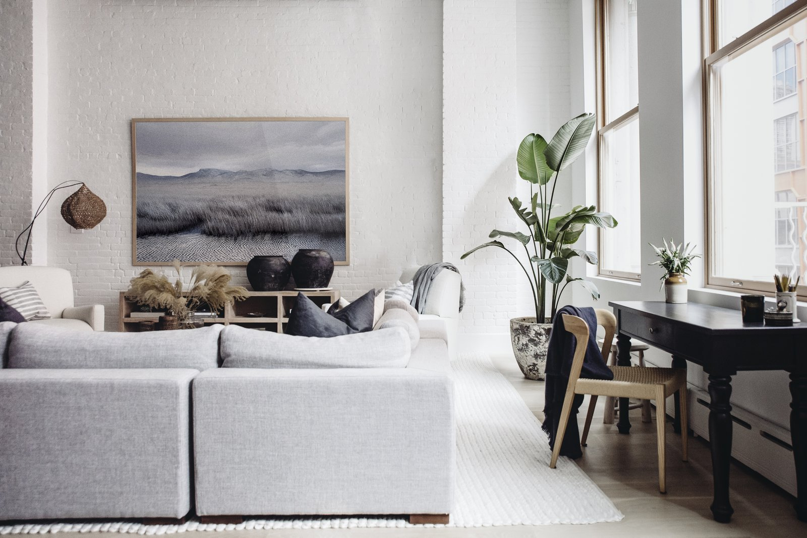 The airy living room shows off a monochrome landscape by Petros Koublis framed by an Interior Define sectional and Verellen coffee table. Extra accents include a floor lamp by Bungalow Decor in Westport, block print pillows by Susan Connor, aerrain plant pot, and black urns by Habitat Greenwich. Tying the space together is a rug from Restoration Hardware. (Chloe Leroux)