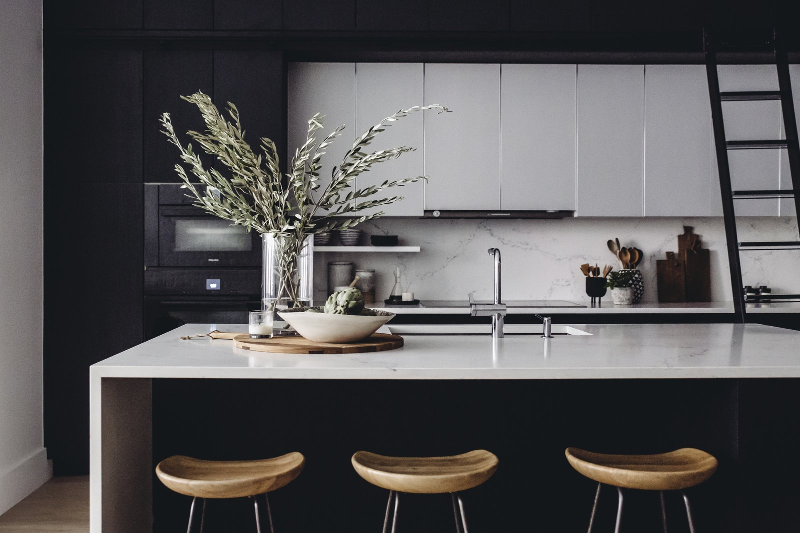 Contrast continues in the kitchen with a black-and-white palette warmed by natural wood elements. A Caesarstone countertop and backsplash with alabaster cabinets add a bright pop to the otherwise inky space—even the Miele and SubZero appliances are in dark tones. Arranged throughout are an Etu Home pizza board, Terrain ceramic fruit bowl, Waterworks cannisters, West Elm mortar and pestle, and a House Dr. utensil pot. (Chloe Leroux)