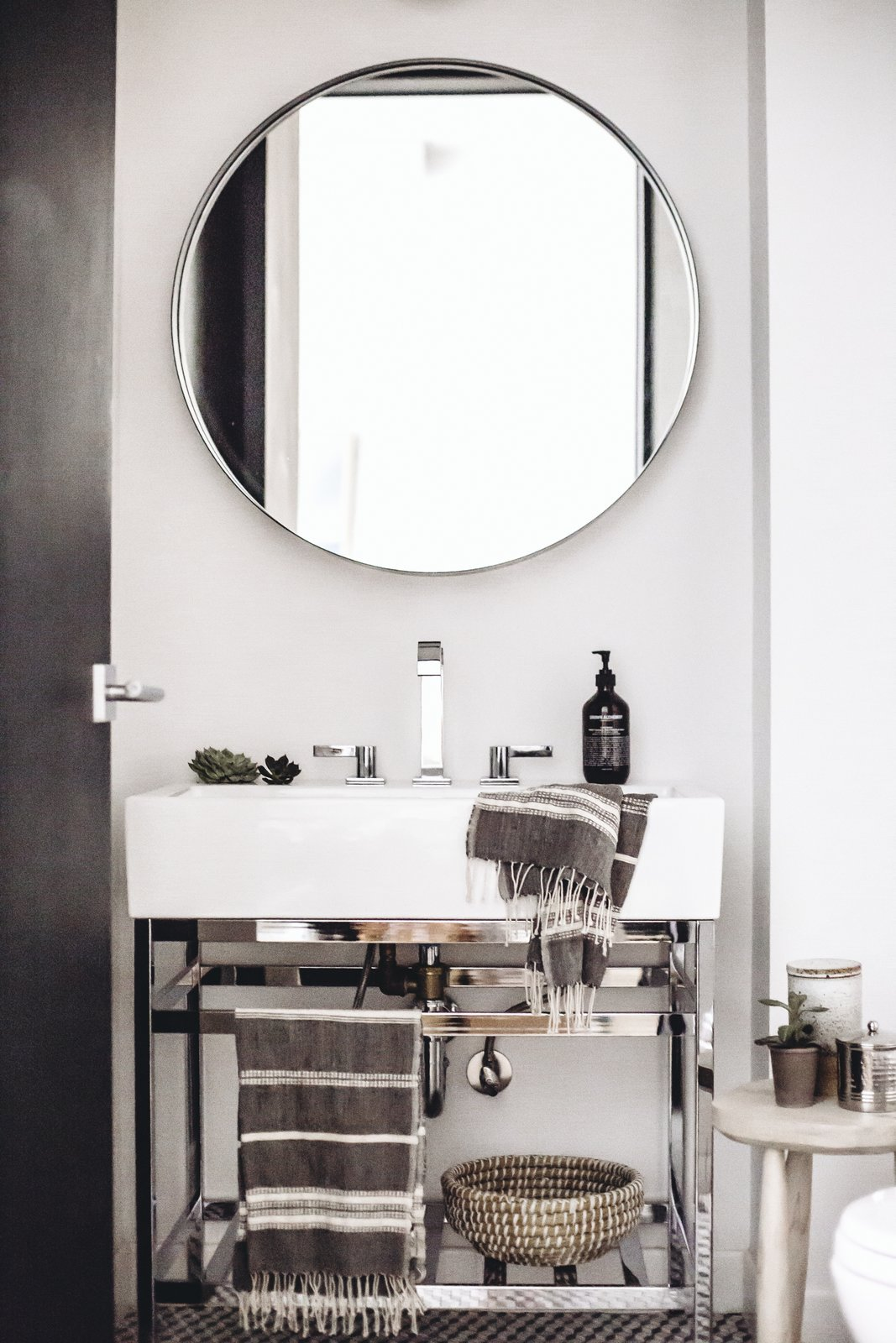 The stone-hued palette makes its way into the powder room where minimalist style is matched with luxurious textiles from Creative Women and silver finishings. A Pottery Barn vanity offers a foundation for a Dornbracht faucet and Grown Alchemist soap. (Chloe Leroux)