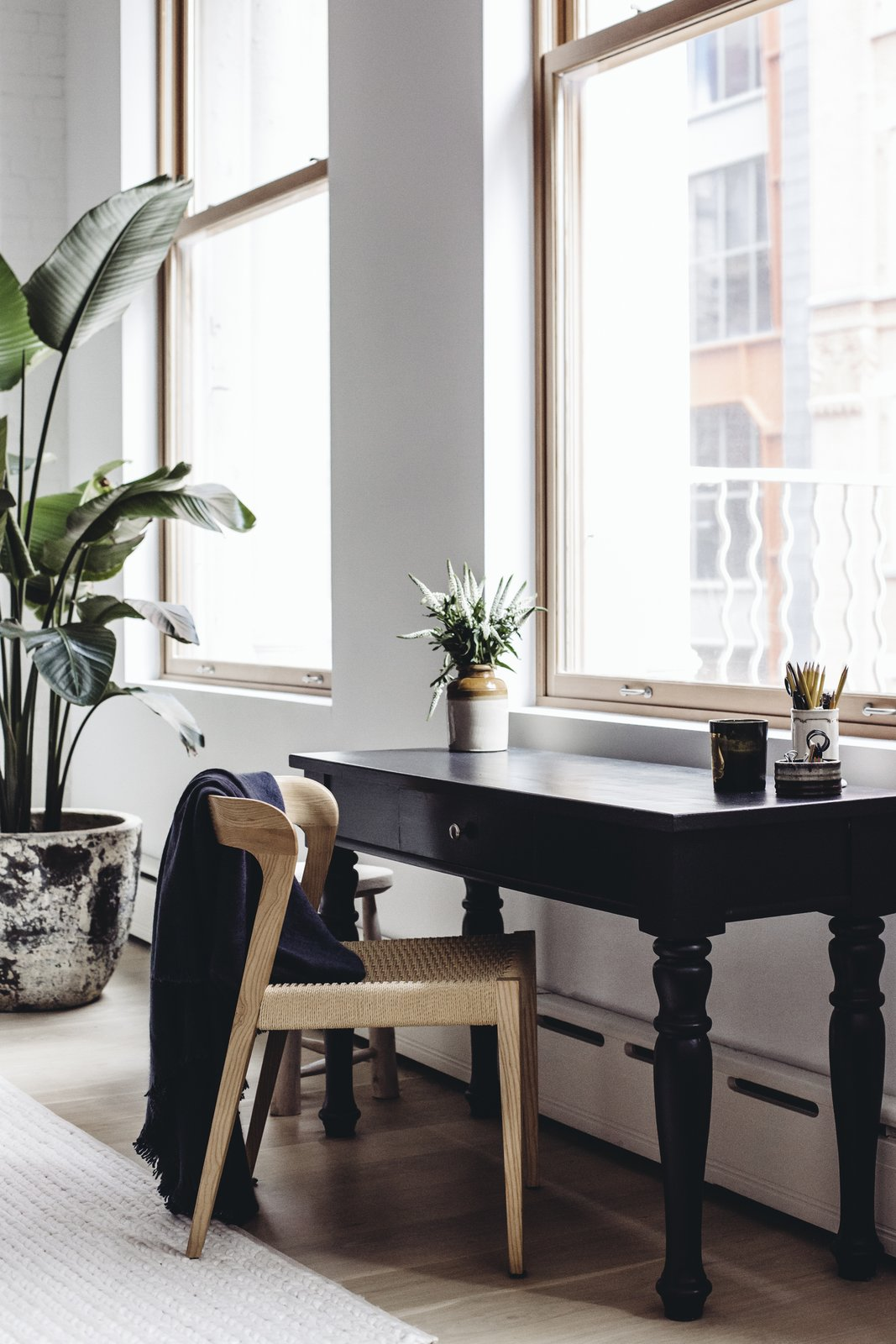 A quiet workspace with black mango wood gear table by Club CU sits in the living room, overlooking the city. (Chloe Leroux)