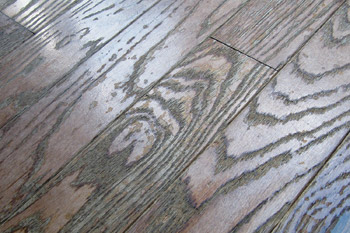 A prefinished solid wood floor damaged by repeated use of a steam mop cleaner.