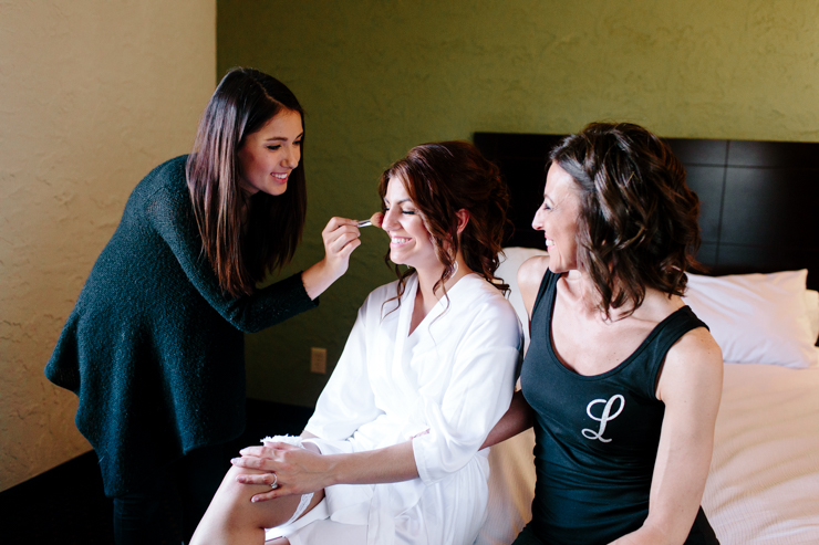 Bride getting her makeup done in a hotel pre-ceremony