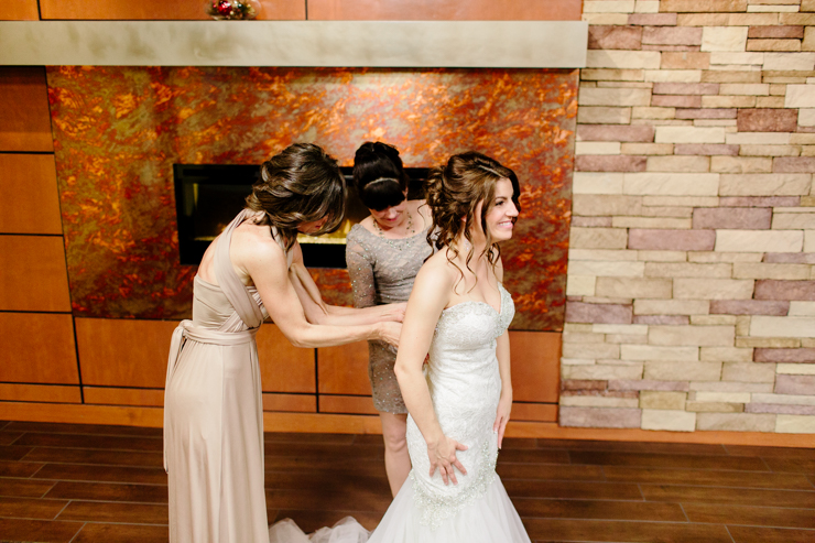 Bride and mothers helping her into her wedding gown on her wedding day