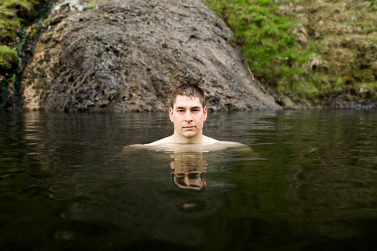man swimming in Seljavallalaug 1923 geothermal pool, Iceland