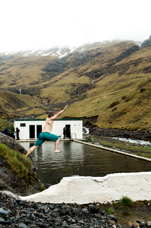 man jumping into Seljavallalaug 1923 geothermal pool, Iceland