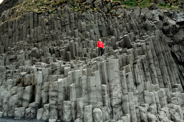 Man standing on basalt columns at Reynisfjara black beach near Vik, Iceland