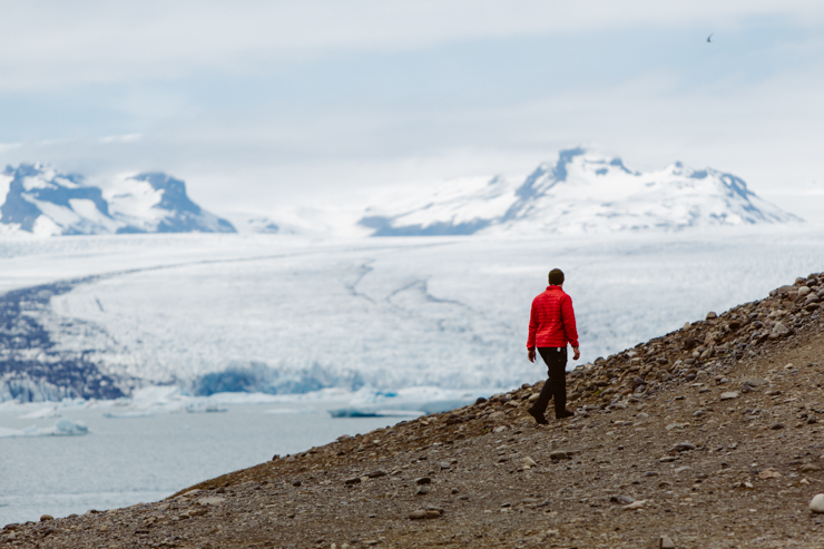 Man in red coat walking near Jokulsarlon Glacier Lagoon, Iceland