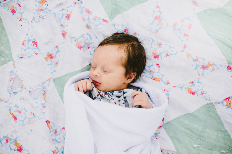 Newborn baby laying on a quilt
