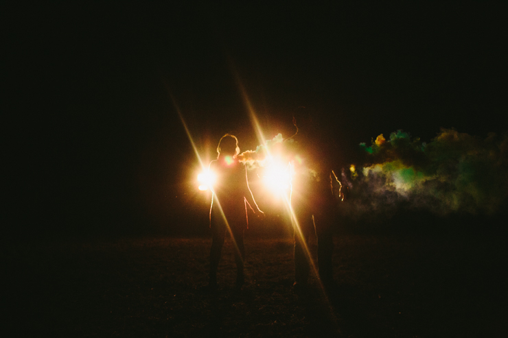 Nolan and Alyssa's Rustic Countryside engagement session dancing with smoke bombs in the headlights of a truck