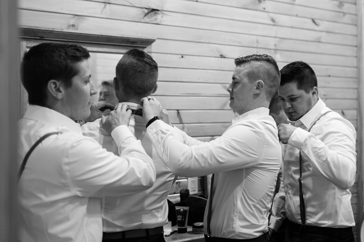 groom getting ready with his groomsmen in a shed