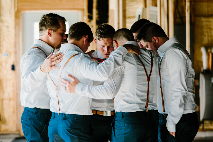 Groomsmen all praying before the outdoor wedding ceremony