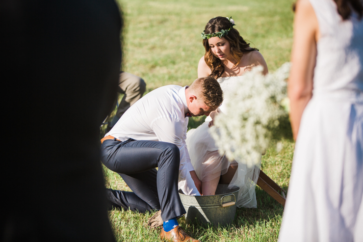 Groom washing the bride's feet during outdoor wedding ceremony