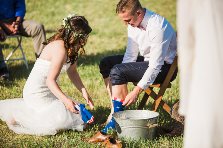 Bride washing groom's feet at outdoor countryside wedding ceremony