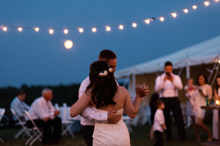 bride and groom's first dance outdoor countryside wedding reception in a big white tent