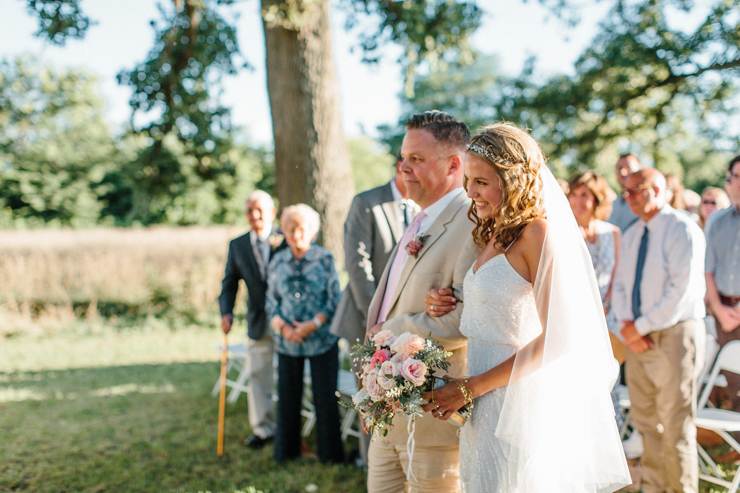 Bride walking down the aisle with her father outdoors and grandparents' farm