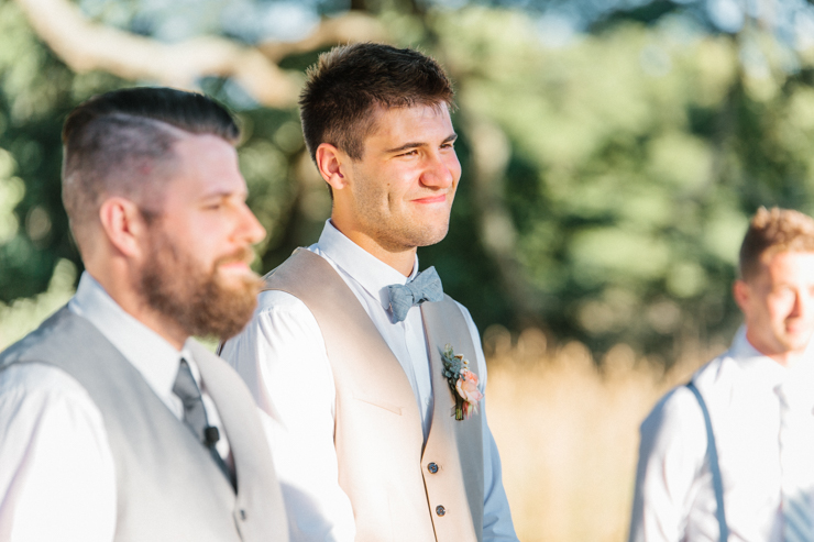 Groom as he sees his bride walk down the aisle for the first time at outdoor ceremony at grandparents' farm