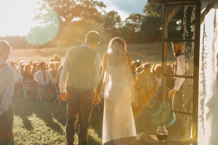 Bride and groom saying vows at outdoor wedding ceremony at sunset on grandparents' farm