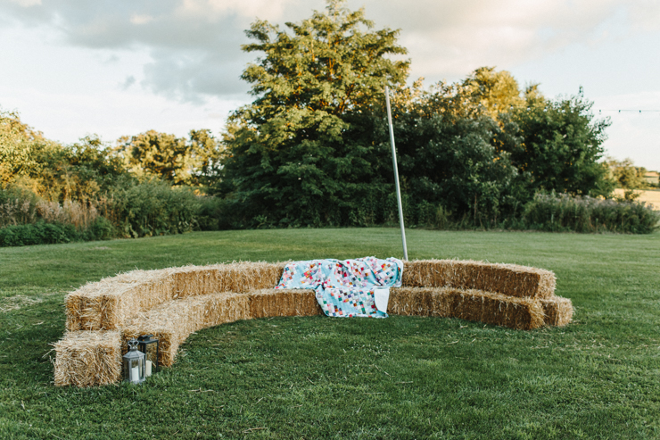 outdoor barn reception seating with hay bales, quilts, and edison bulbs