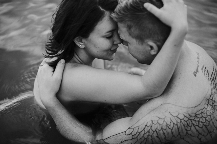 Intimate couple photography. Photography of a married couple with amazing tattoos in the water together partially nude