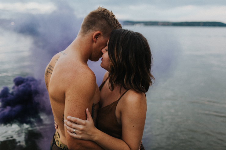 Intimate couple photography nude in the water with a purple photography smoke bomb