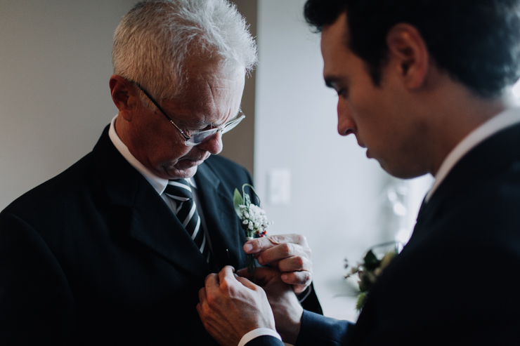 Groom helping his father get ready day of wedding