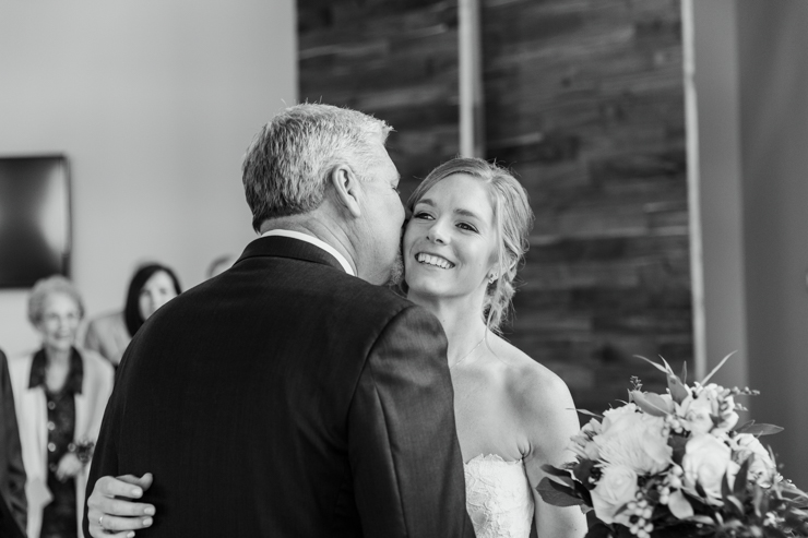 Father kissing daughter at wedding