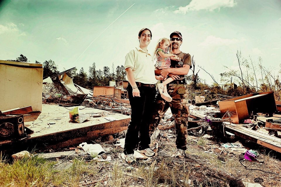 Kevin's house was in a valley outside of the town. Half of his property was destroyed with Tornado #1 and the second half was destroyed with Tornado #2. In spite of that he remained a positive guy as he stands with his wife and daughter for a portrait.