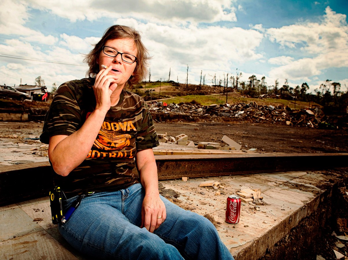 Yvonne - this picture says it all. Yvonne is sitting where The Rebel Queen used to be. She was a waitress there and her husband owned the business. On April 27, 2011 she sought quick shelter from tornado #2 (the worst one) inside the men's room - but had the wherewithal to remember here 12 pack of Coca-Cola! Nothing was left of the Rebel Queen except the men's room where she had been. When leaving she turned around to find a Jeep was on top of the men's room but was being held up by a bent pipe - the pipe Yvonne had been underneath.