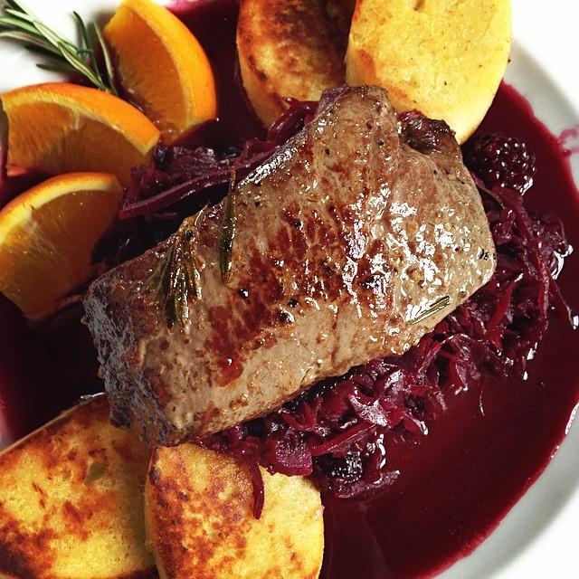 Deer steak on blackberries with red cabbage