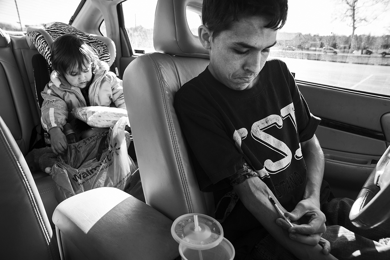 Nathan, 19, of Jackson, Ohio, injects heated black tar heroin into his vein while pulled over in a grocery store parking lot on November 13, 2013. A self-professing 'addict', Nathan uses heroin to help combat the pain of his severe Scoliosis and Neurofibromatosis, for which he has undergone several corrective surgeries. Nathan's daughter, Mallori, 2, is yet to realize the struggle her father faces.