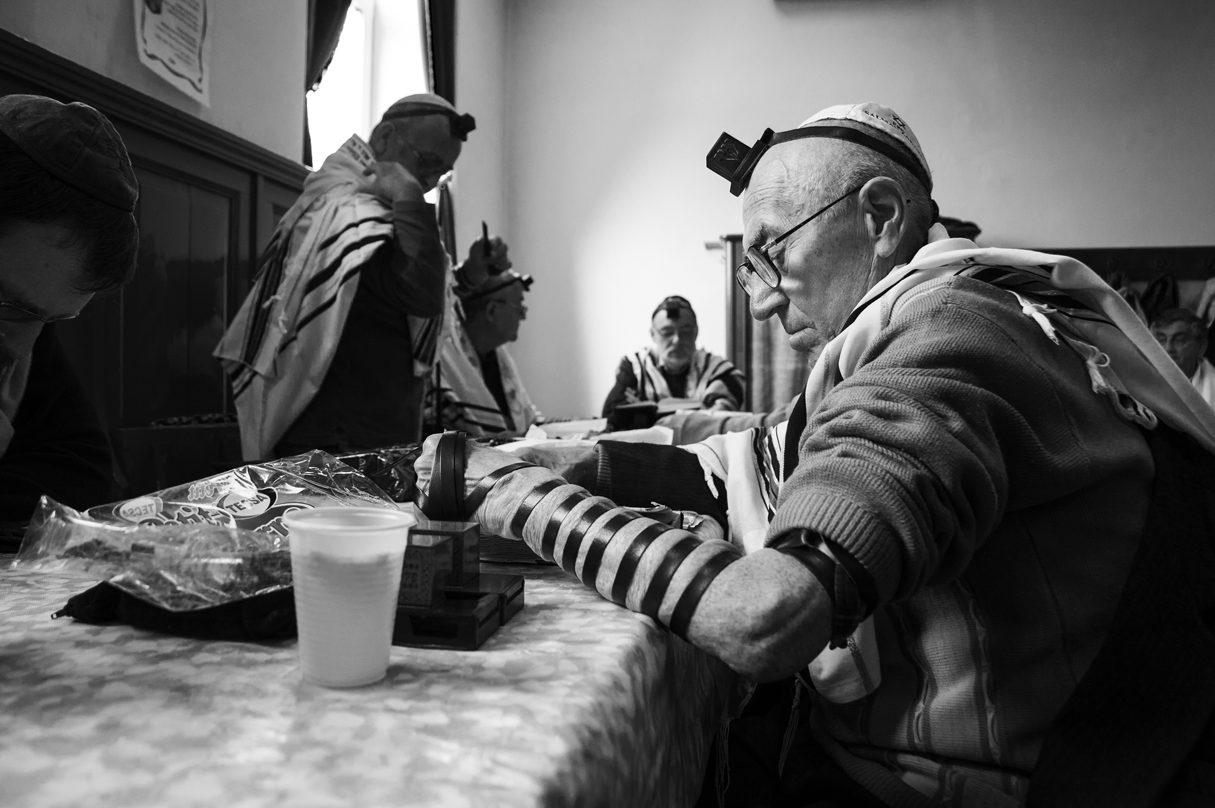 Zakaria Salman studies a religious text with the other members of the minyan in Oradea's only remaining active Sas Chevra Synagogue on April 11, 2013.