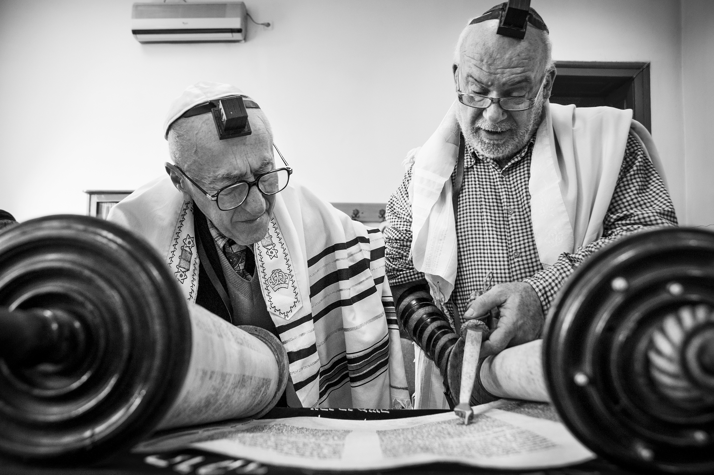 Community member, Zakaria Salman, left, and Cantor Shraya Kav, right, read from the Torah scroll during the daily morning meeting at the Sas Chavra Synagogue on April 11, 2013. Though not officially a rabbi, Kav, a cantor from Tel Aviv, performs many of daily duties of a rabbi for the small community.