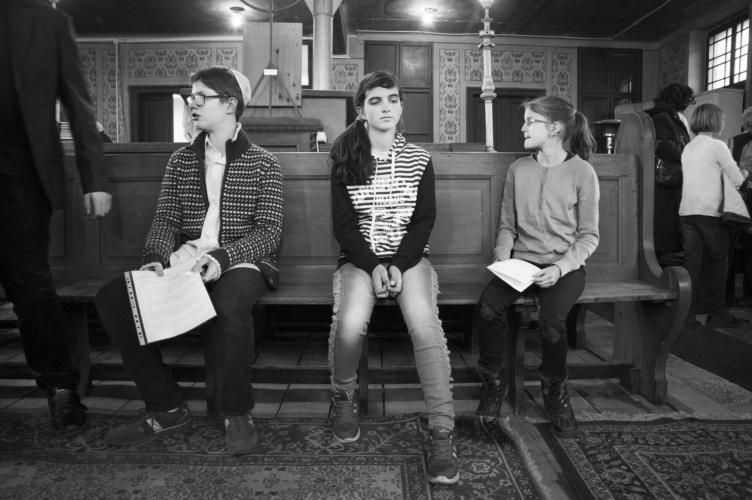 Three children wait as the community president prepares to speak to them about their responsibility to continue the ancient religious traditions of the Jewish people before their Bar and Bat Mitzvah ceremonies on January 16, 2015.