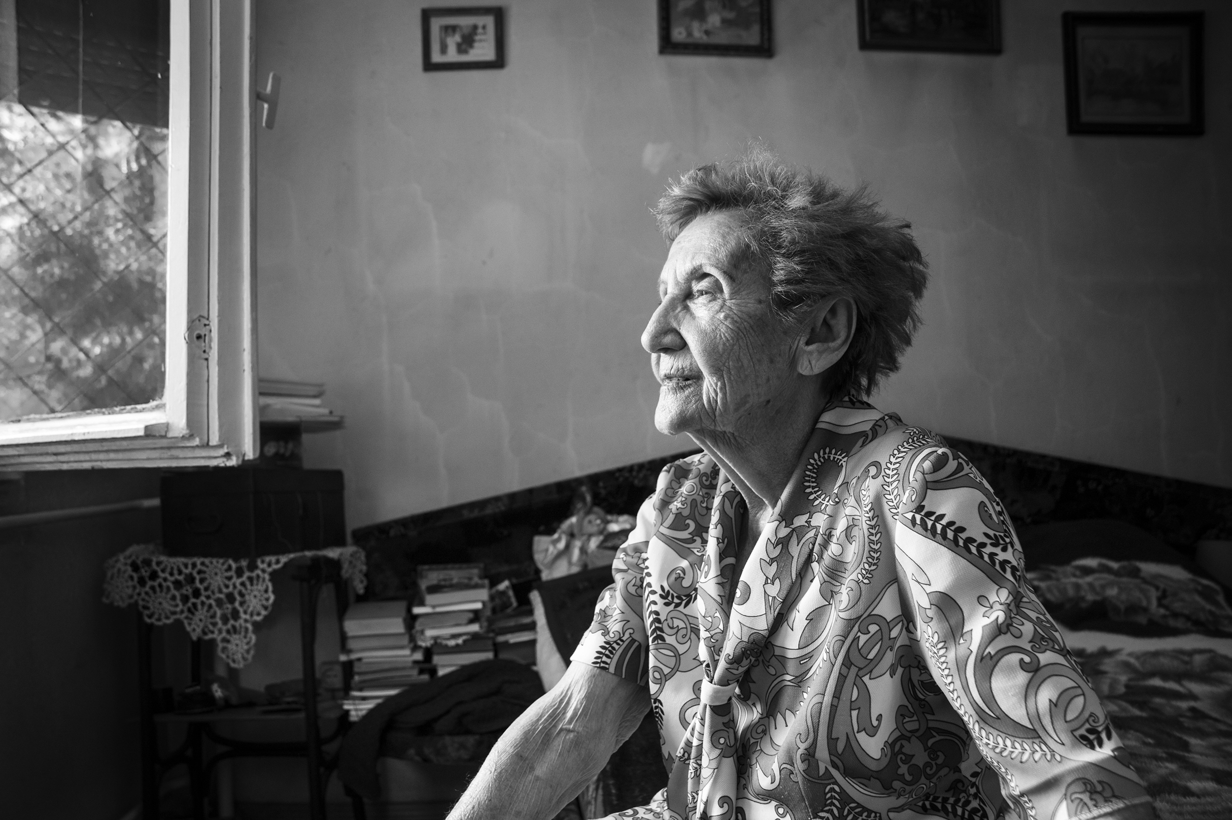 """Gabriella (Hamlet) Bóné, a survivor of Auschwitz Birkenau, sits on her bed and looks out the window of her small ground-level apartment in Oradea, Romania on August 23, 2013. Bóné vividly remembers the deportations when she was just fifteen years old. """"The Hungarian police crammed us into wooden train cars that had barbed wire covering the small windows. We traveled without food and with very little water for nearly a week without knowing what fate lay before us. We arrived at Auschwitz having barely slept only to be inspected by Dr. Mengele himself and the other SS officers."""""""
