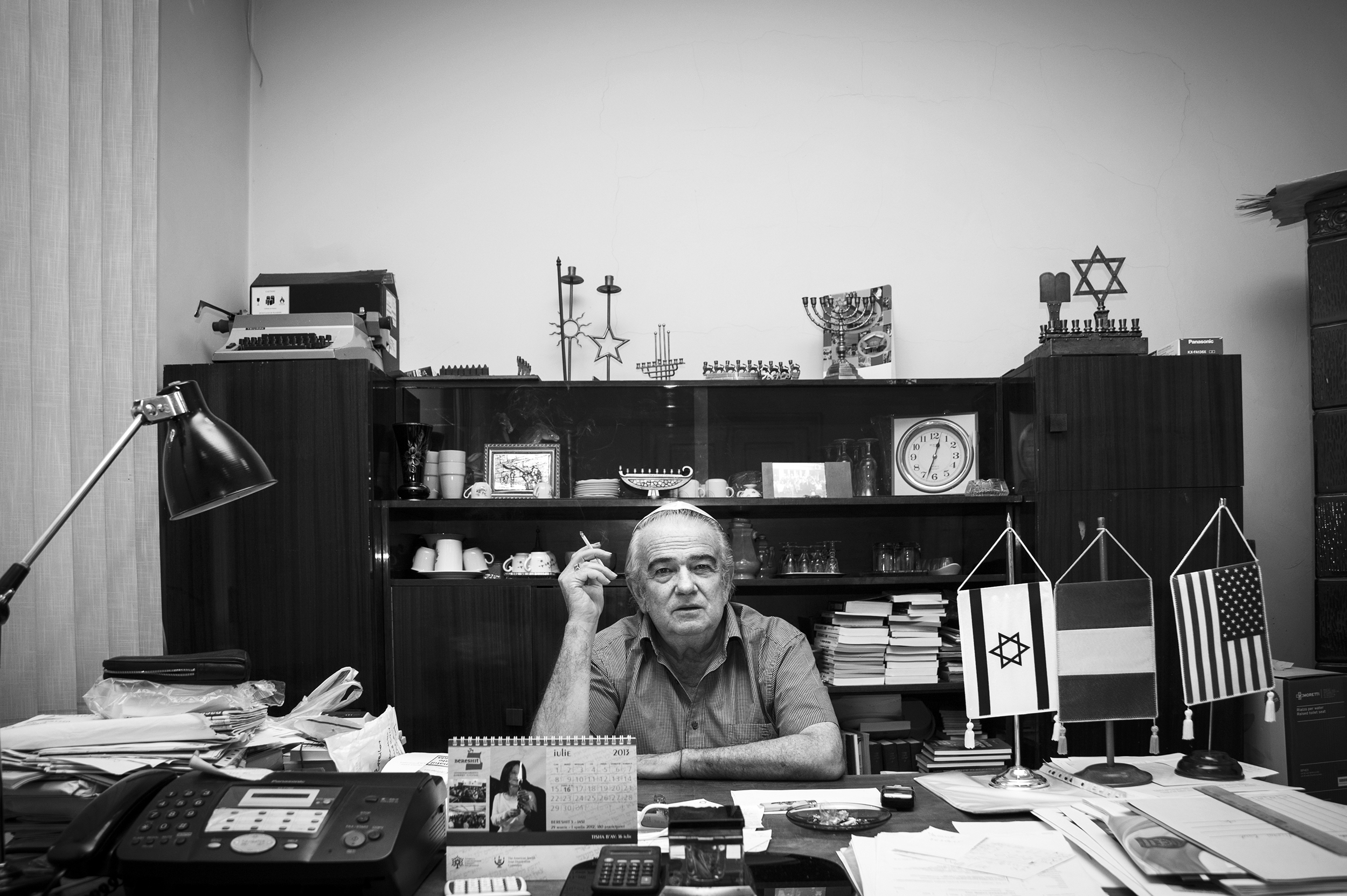 Teodor Koppelmann, President of the Jewish Community Center in Oradea, Romania, sits behind his cluttered desk where he often chains-mokes while overseeing the day-to-day business and attending to the needs of his community members on August 26, 2013.