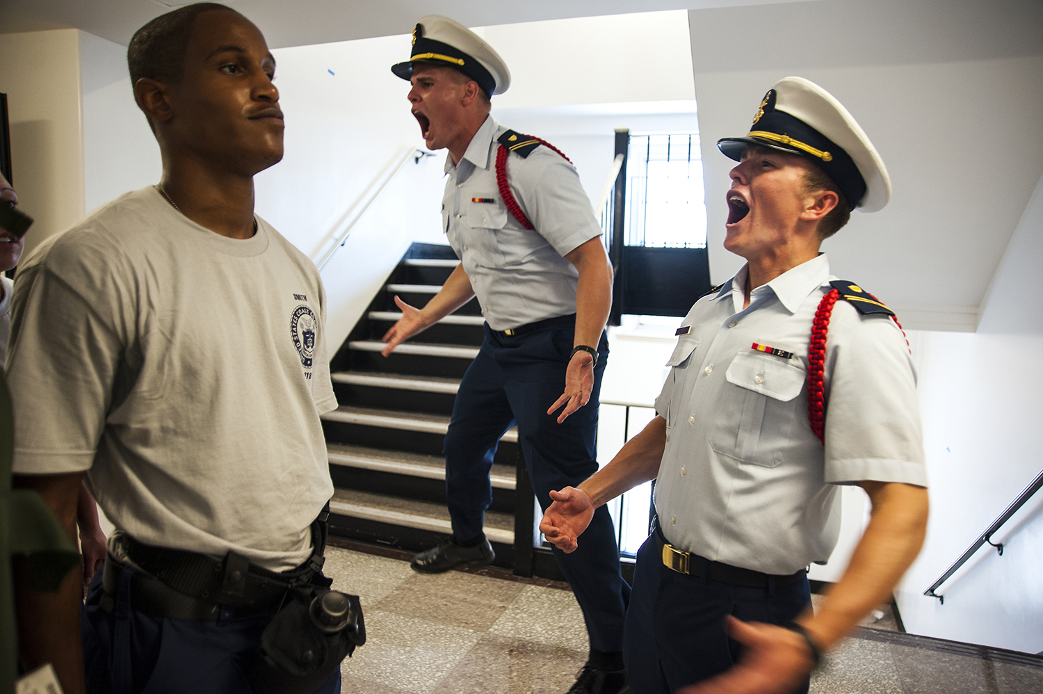 NEW LONDON- 06302014-- Swab Che Smith (left) of Horn Lake, MS receives an immediate and sharp rebuke from Delta Company Cadres, Lobmeyer, center, and Hirst, right, during R-Day during the United States Coast Guard Academy's Swab Summer in New London on Monday, June 30, 2014.(DANIEL OWEN | The Hartford Courant)