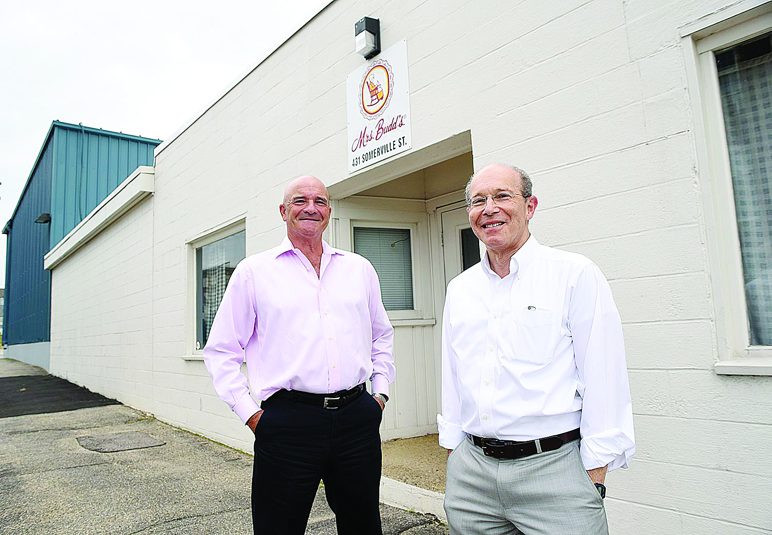 Mrs. Budd's owners Leo Sprecher, right, and Curt Marcott in front of the company's Manchester plant on Somerville Street on Tuesday.(DAVID LANE/UNION LEADER)