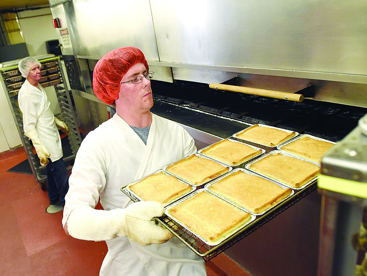 9/8/15--Adam Miller of Manchester removes a tray of chicken pies from the oven at Mrs. Budd's in on Tuesday. DAVID LANE/UNION LEADER
