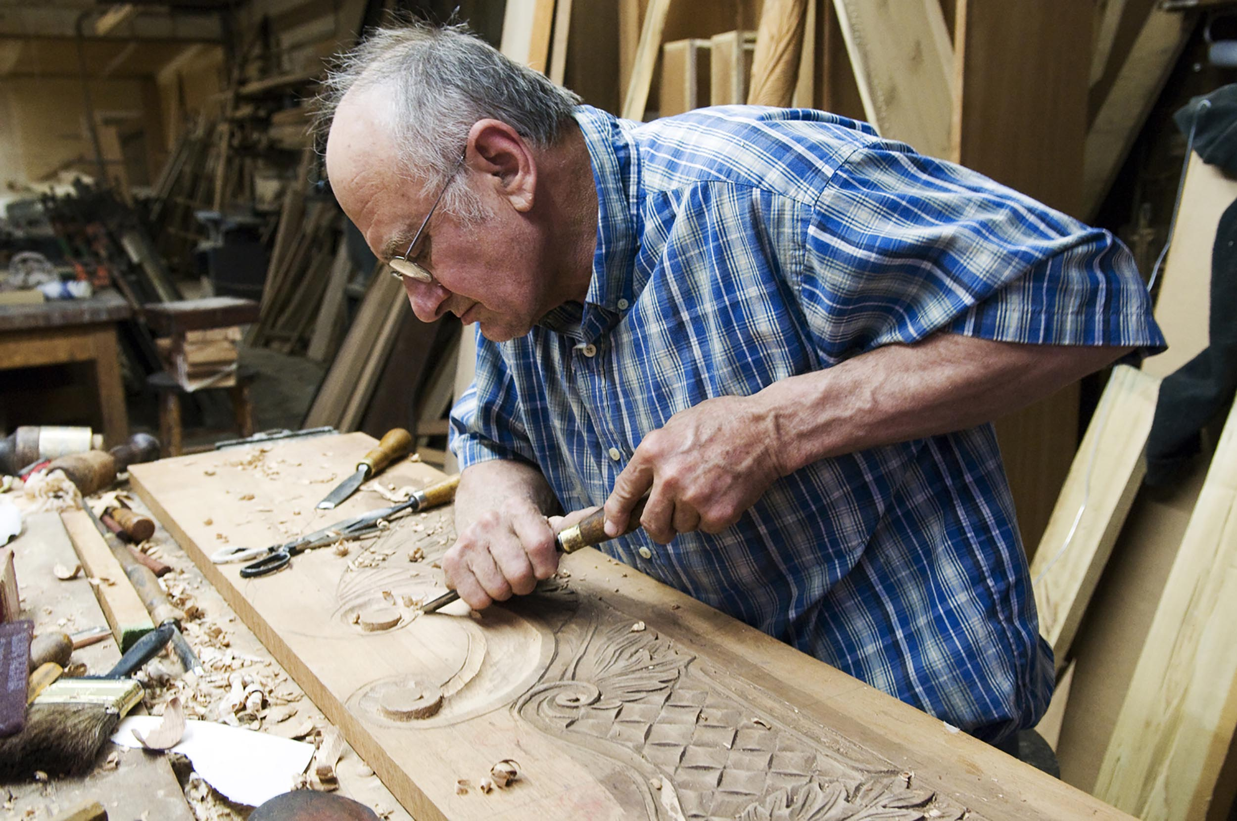 Joe Mazurek carves a headboard out of a peice of maghony at his shop in Camden, S.C. He uses 18th century construction techniques to build furniture.