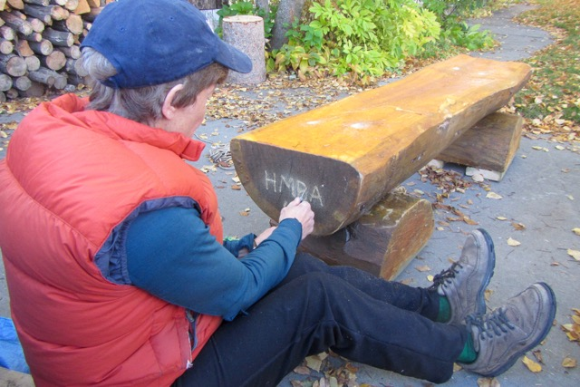 """Maureen etches """"HMBA 16"""" onto the bench destined for the EZ Lookout."""